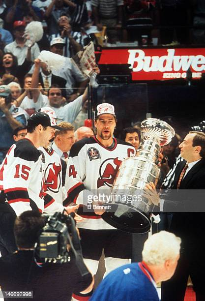 Scott Stevens of the New Jersey Devils takes the Stanley Cup from NHL commissioner Gary Bettman after the Devils defeated the Detroit Red Wings in...