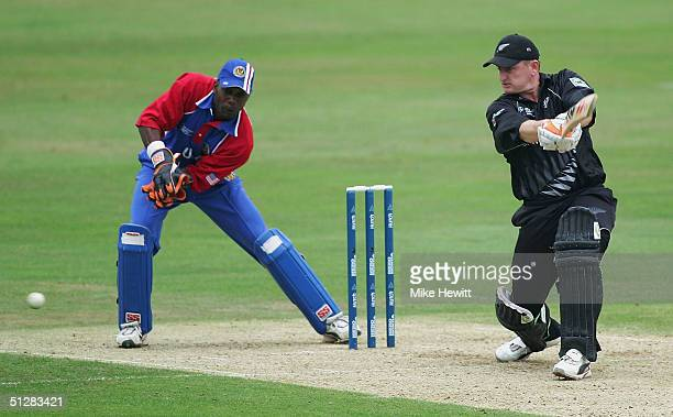 Scott Styris of New Zealand drives for four as Mark Johnson of USA looks on during the ICC Champions Trophy match between New Zealand and USA on...