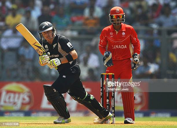 Scott Styris of New Zealand hits the ball towards the boundary as Ashish Bagai of Canada looks on during the 2011 ICC World Cup match between Canada...