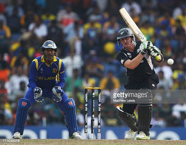 Scott Styris of New Zealand hits the ball towards the boundary as Kumar Sangakkara of Sri Lanka looks on during the 2011 ICC World Cup SemiFinal...