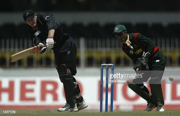Scott Styris of New Zealand in action watched by Khaled Mashud of Bangladesh during the ICC Champions Trophy match between New Zealand and Bangladesh...