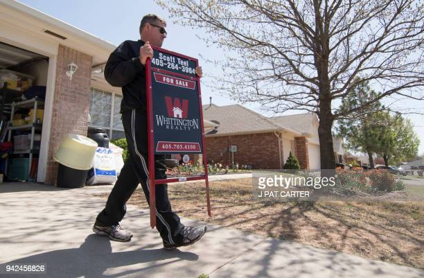 Scott Teel a high school history teacher carries a 'for sale' sign as part of his second job as a real estate agent in Moore Oklahoma on April 4 2018...
