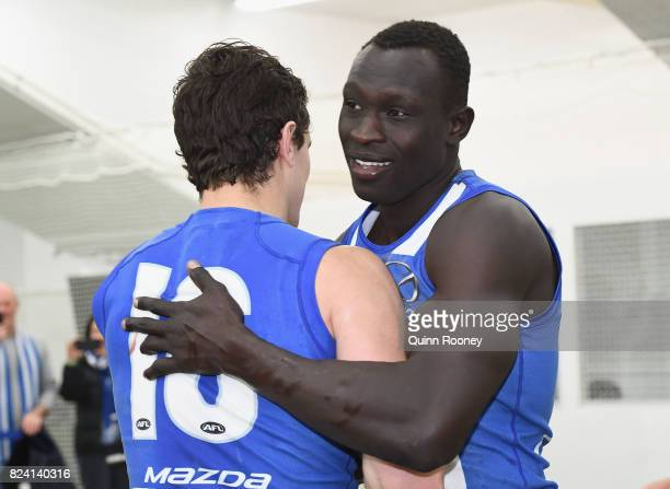 Scott Thompson and Majak Daw of the Kangaroos celebrate in the rooms after winning the round 19 AFL match between the North Melbourne Kangaroos and...
