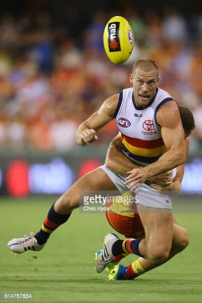 Scott Thompson of the Crows handballs while being tackled during the NAB Challenge AFL match between the Gold Coast Suns and the Adelaide Crows at...