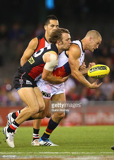 Scott Thompson of the Crows handballs whilst being tackled by Josh Saunders of the Saints during the round four AFL match between the St Kilda Saints...