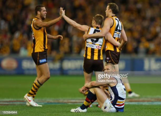 Scott Thompson of the Crows looks dejected as Lance Franklin Sam Mitchell and David Hale of the Hawks celebrates winning the second AFL Preliminary...