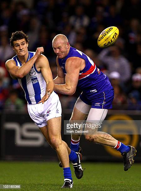 Scott Thompson of the Kangaroos handballs as Barry Hall of the Bulldogs lays a tackle during the round 18 AFL match between the Western Bulldogs and...