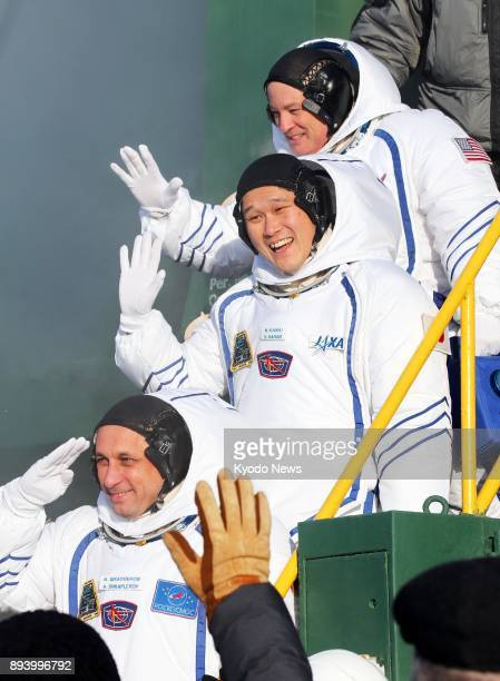Scott Tingle of the United States Norishige Kanai of Japan and Anton Shkaplerov of Russia wave to onlookers before boarding a Soyuz spacecraft in...