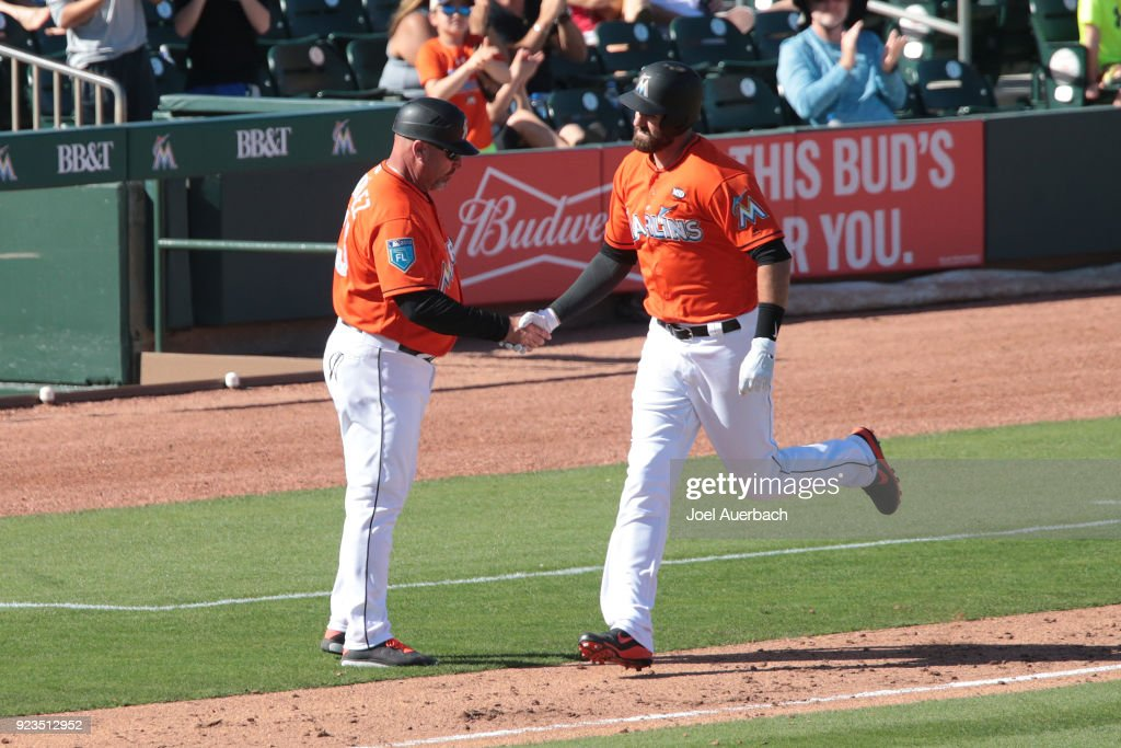 Scott Van Slyke #5 is congratulated by third base coach Fredi Gonzalez #33 of the Miami Marlins as he rounds the bases after hitting a seventh inning grand slam home run against the St Louis Cardinals during a spring training game at Roger Dean Chevrolet Stadium on February 23, 2018 in Jupiter, Florida. The Marlins defeated the Cardinals 6-4.