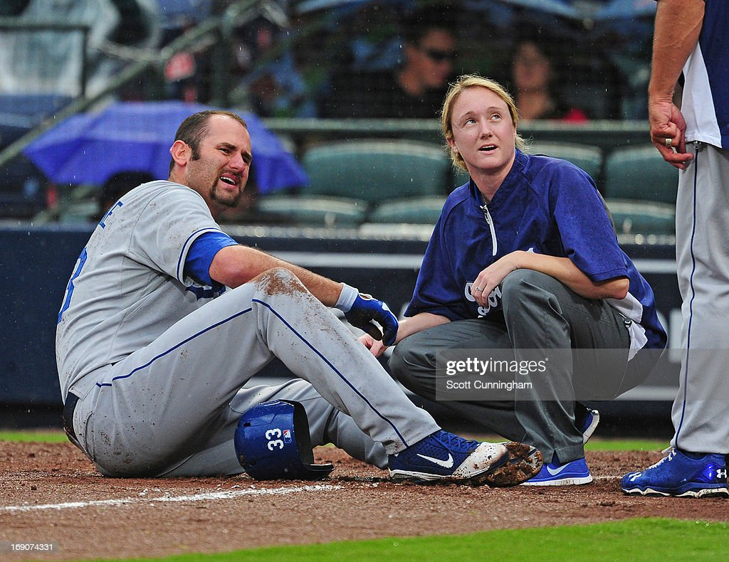 Scott Van Slyke #33 of the Los Angeles Dodgers is attended to by a trainer after fouling a ball off of his foot during the game against the Atlanta Braves at Turner Field on May 19, 2013 in Atlanta, Georgia.