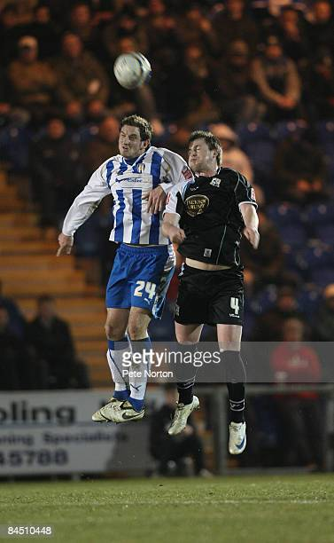 Scott Vernon of Colchester United heads the ball under pressure from Mark Hughes of Northampton Town during the Coca Cola League One Match between...