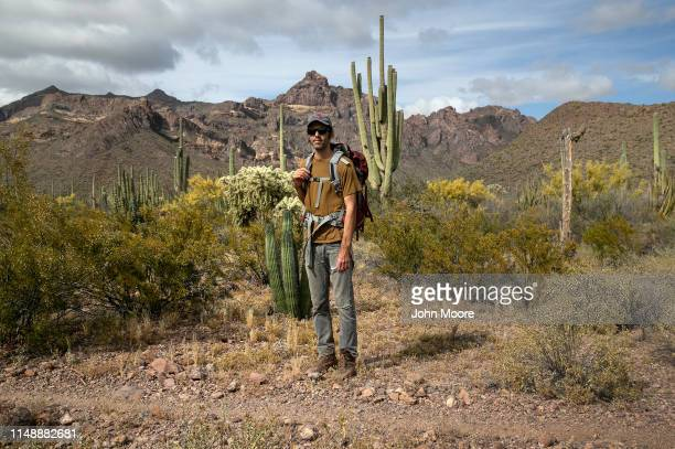 Scott Warren a volunteer for the humanitarian aid organization No More Deaths pauses while delivering food and water along remote desert trails used...