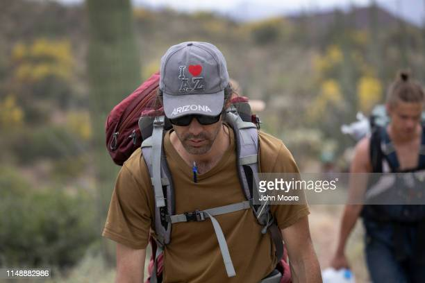 Scott Warren a volunteer for the humanitarian aid organization No More Deaths hikes with fellow volunteers while delivering food and water along...