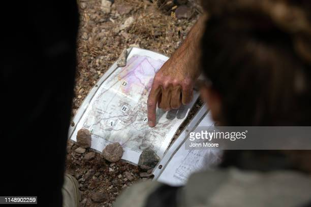 Scott Warren a volunteer for the humanitarian aid organization No More Deaths goes over a map of migrant trails with volunteers delivering food and...