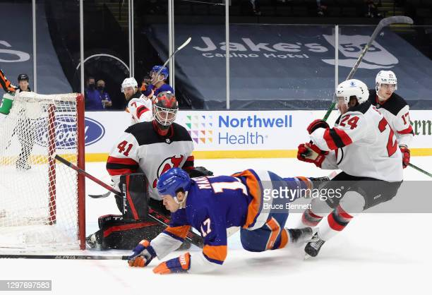 Scott Wedgewood and Ty Smith of the New Jersey Devils defend against Matt Martin of the New York Islanders during the second period at Nassau...
