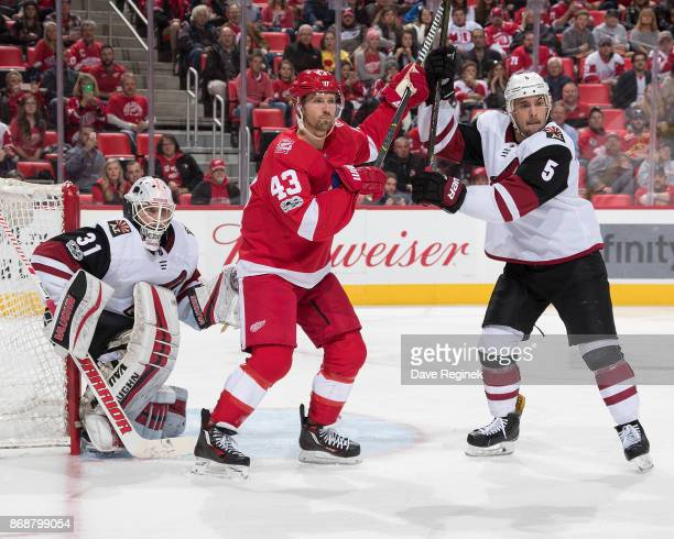 Scott Wedgewood of the Arizona Coyotes is screened by Darren Helm of the Detroit Red Wings as he battles for position with Adam Clendening of the...