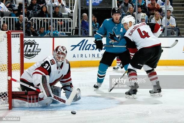 Scott Wedgewood of the Arizona Coyotes protects the net as Niklas Hjalmarsson of the Arizona Coyotes defends Logan Couture of the San Jose Sharks at...