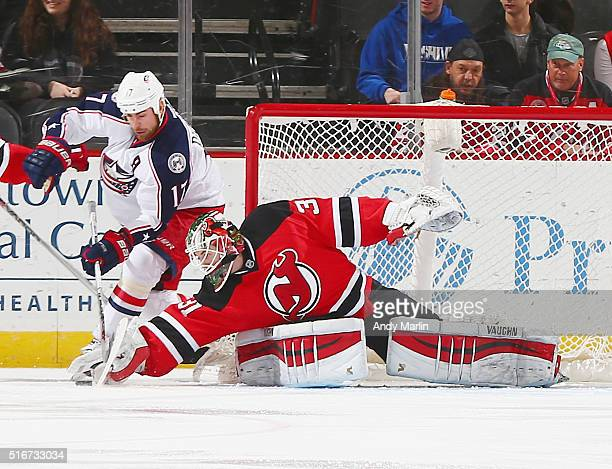 Scott Wedgewood of the New Jersey Devils playing in his first NHL game makes a save against Brandon Dubinsky of the Columbus Blue Jackets during the...