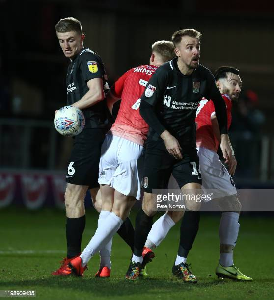 Scott Wharton and Chris Lines of Northampton Town look for the ball with Luke Armstrong of Salford City during the Sky Bet League Two match between...