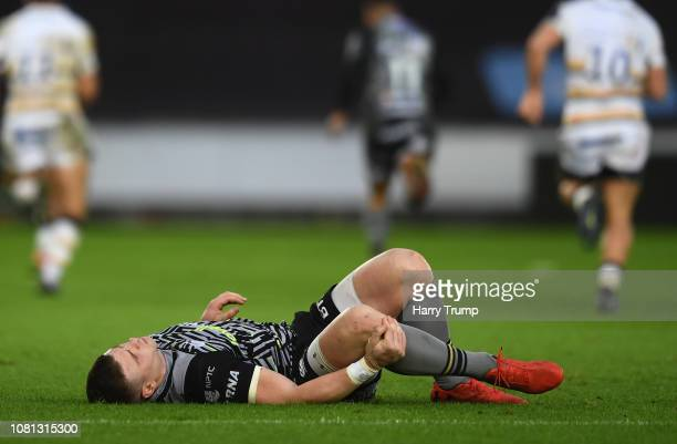 Scott Williams of Ospreys lies on the floor and receives medical attention during the Challenge Cup match between Ospreys and Worcester Warriors at...
