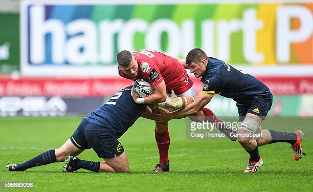 Scott Williams of Scarlets is tackled by Niall Scannell of Munster during the Guinness PRO12 Round 1 match between Scarlets and Munster Rugby at Parc...