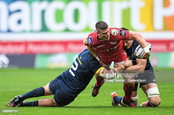 Scott Williams of Scarlets offloads the ball despite tackle of Niall Scannell and Jack O'Donoghue of Munster during the Guinness PRO12 Round 1 match...