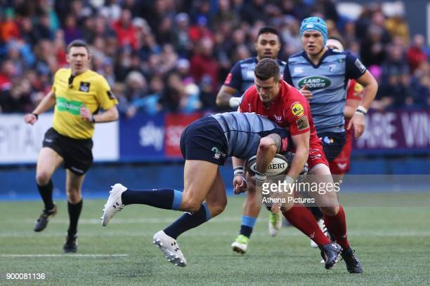 Scott Williams of Scarlets tackles Tom James of Cardiff Blues during the Guinness Pro 14 match between Cardiff Blues and Scarlets at the Cardiff Arms...