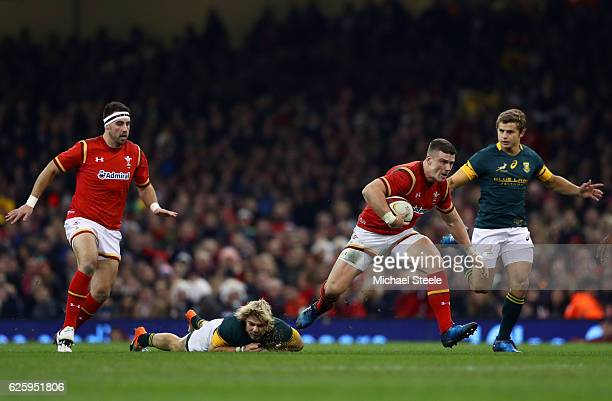 Scott Williams of Wales runs past a tackle by Faf de Klerk of South Africa during the international match between Wales and South Africa at...