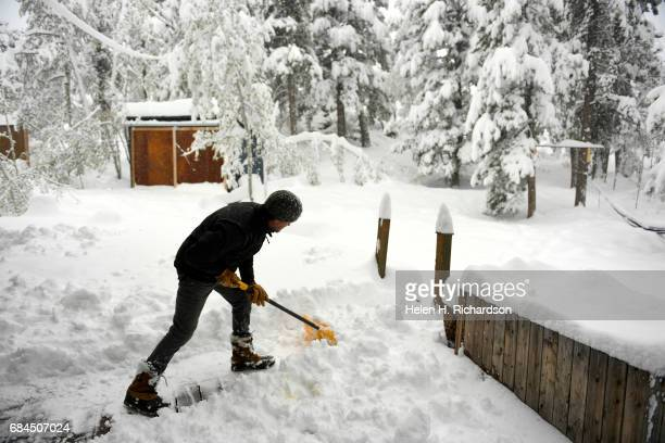 Scott Willimack shovels snow off of his deck where more than 18 inches of snow has fallen in his backyard in less than 24 hours on May 18 2017 in...