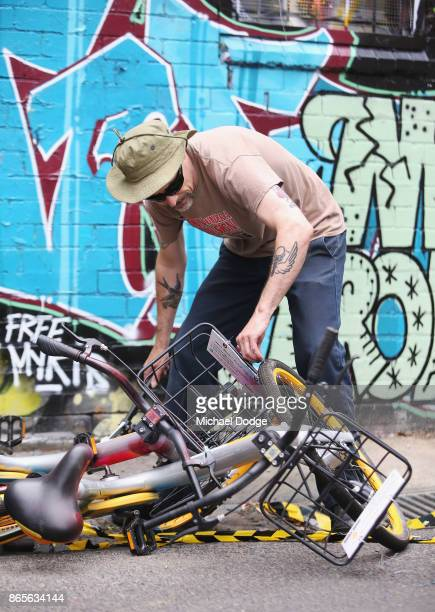 Scott Wilson a ''bike wrangler'' hired by oBike dismantles an art installation that was stuck to a brick wall in a lane way in Fitzroy on October 24...