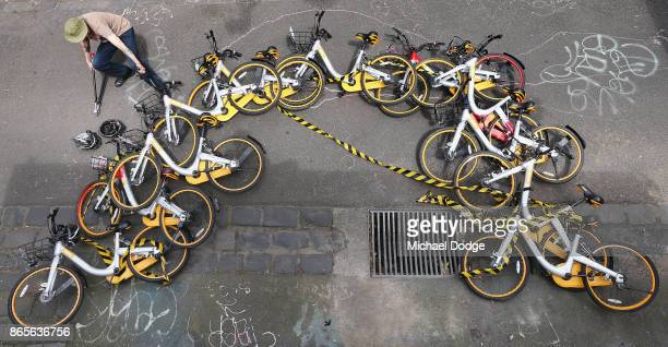 Scott Wilson a ''bike wrangler'' hired by oBike dismantles an art installationt that was stuck to a brick wall by an unknown artist in a lane way in...