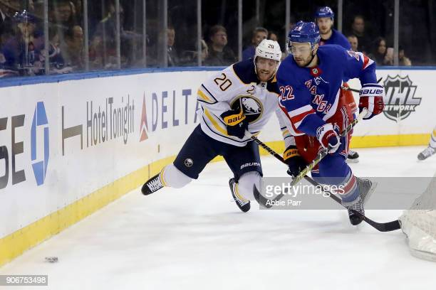 Scott Wilson of the Buffalo Sabres battles for the puck against Kevin Shattenkirk of the New York Rangers in the first period during their game at...