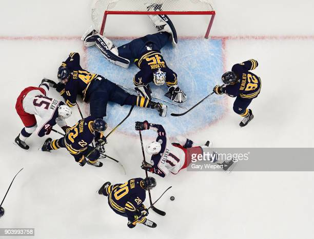 Scott Wilson of the Buffalo Sabres gathers a loose puck against Matt Calvert of the Columbus Blue Jackets and during an NHL game on January 11 2018...