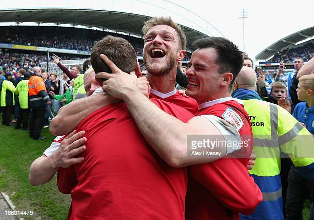 Scott Wiseman of Barnsley celebrates survival with team mates at the end of the npower Championship match between Huddersfield Town and Barnsley at...