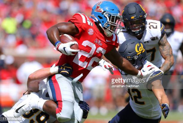 Scottie Phillips of the Mississippi Rebels runs with the ball as Evan Weaver of the California Golden Bears and Myles Jernigan defend and during the...
