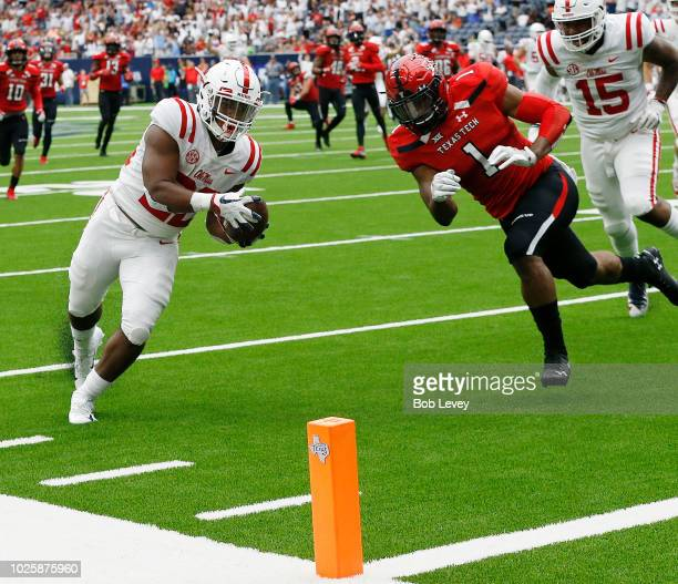 Scottie Phillips of the Mississippi Rebels scores in the second quarter as Jordyn Brooks of the Texas Tech Red Raiders attempts to keep him out ot...