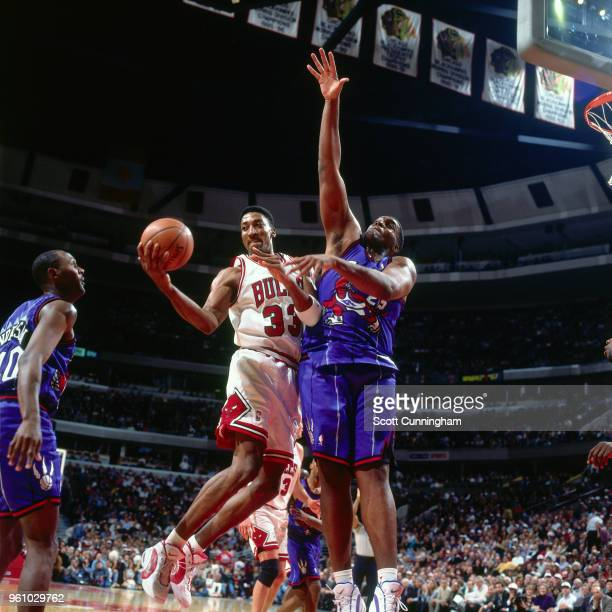 Scottie Pippen of the Chicago Bulls goes to the basket against Oliver Miller of the Toronto Raptors on November 7 1995 at the United Center in...