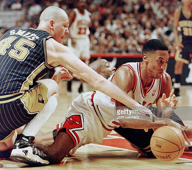 Scottie Pippen of the Chicago Bulls scrambles for a loose ball with Rik Smits of the Indiana Pacers 27 May during the first half of game five of...