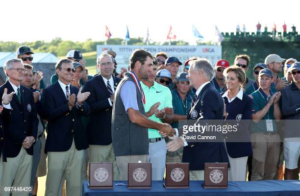 Scottie Scheffler of the United States is presented with the low amateur medal after the final round of the 117th US Open Championship at Erin Hills...