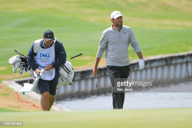 Scottie Scheffler walks with his caddie along the 12th hole during the semifinal match at the World Golf Championships-Dell Technologies Match Play...