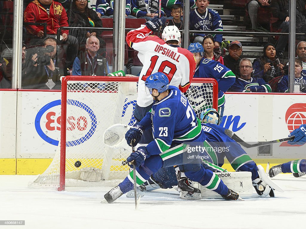 Scottie Upshall #19 of the Florida Panthers and Alexander Edler #23 of the Vancouver Canucks watch the puck enter the goal behind Roberto Luongo #1 of the Canucks during their NHL game at Rogers Arena on November 19, 2013 in Vancouver, British Columbia, Canada.