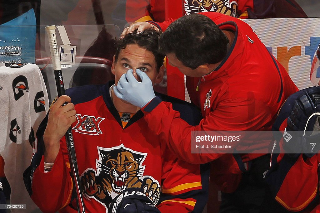Scottie Upshall #19 of the Florida Panthers has his nose put back in the right place by David Zenobi - Head Athletic Trainer during a break in the action against the washington Capitals at the BB&T Center on February 27, 2014 in Sunrise, Florida.