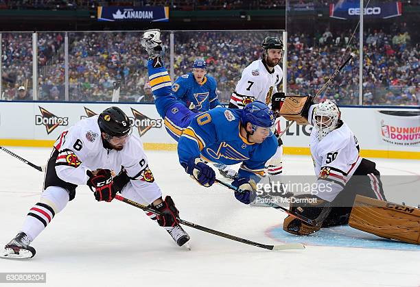Scottie Upshall of the St Louis Blues is upended during the 2017 Bridgestone NHL Winter Classic against the Chicago Blackhawks at Busch Stadium on...