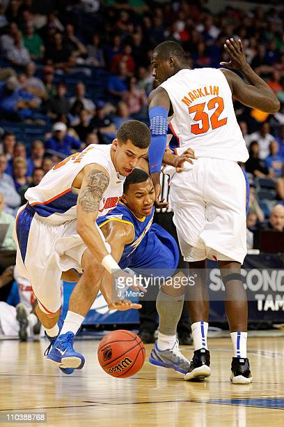 Scottie Wilbekin of the Florida Gators attempts to steal the ball from Orlando Johnson of the UC Santa Barbara Gauchos as Vernon Macklin of the...