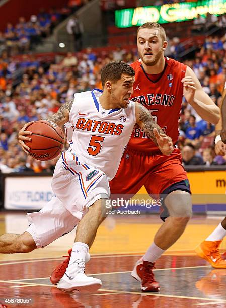 Scottie Wilbekin of the Florida Gators dribbles the ball past Tanner Giddings of the Fresno State Bulldogs during the MetroPCS Orange Bowl Basketball...