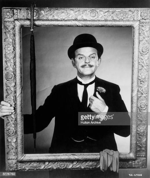 Scottish actor David Tomlinson smiles while posing behind a gilt picture frame in a promotional portrait for director Robert Stevenson's film 'Mary...