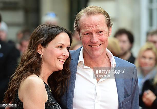Scottish actor Iain Glen and partner Charlotte Emmerson pose on arrival for the premiere of Eye in the Sky in central London on April 11 2016 / AFP /...