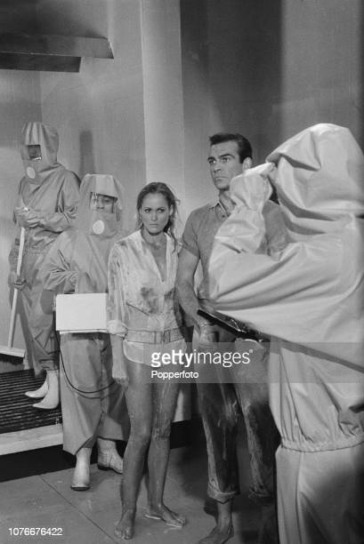 Scottish actor Sean Connery and Swiss born actress Ursula Andress pictured together in character as James Bond and Honey Ryder in a decontamination...