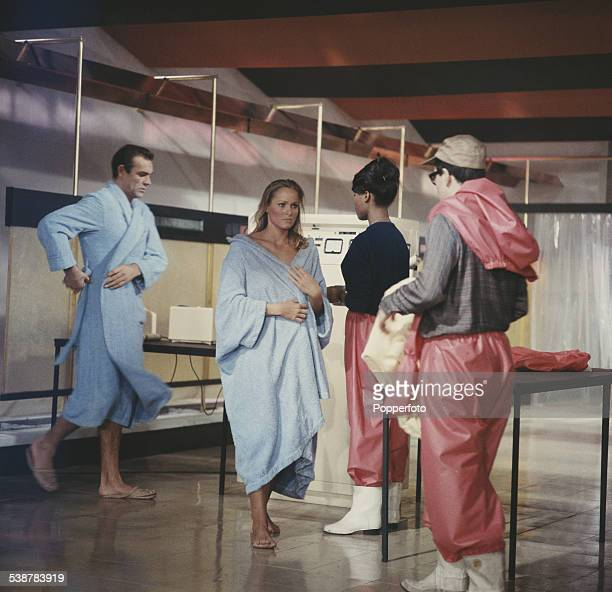 Scottish actor Sean Connery and Swiss born actress Ursula Andress pictured together in character as James Bond and Honey Ryder wearing blue robes...