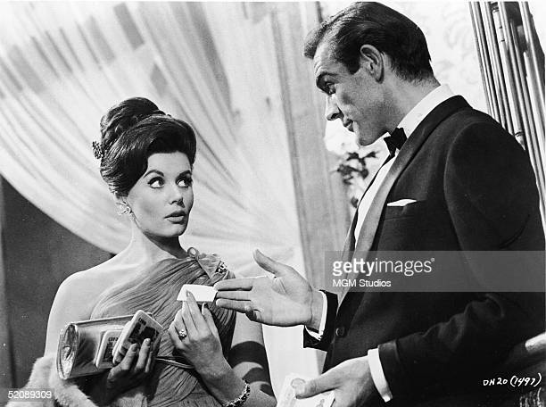 Scottish actor Sean Connery, as fictional secret agent James Bond, hands a business card to British actress Eunice Gayson in a scene from the film...